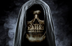 Grim reaper. Portrait of a skull in the hood over black, foggy background Royalty Free Stock Image