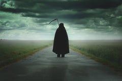 Grim reaper walking a desolate road. Grim reaper walking on a dark desolate road .Halloween and death Stock Images