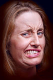 Grimace. Close-up of woman grimacing on dark background royalty free stock image