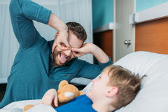 Grimace dad and son having fun. In hospital chamber Stock Photo