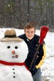 Grimace de garçon couverte dans la neige Images libres de droits