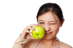 Grimace girl. Asian young woman holding green apple and making a  grimace Stock Images