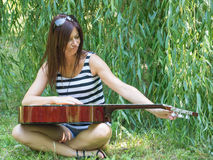 Grimace with guitar. Tough girl grimace on the grass with guitar Stock Photo