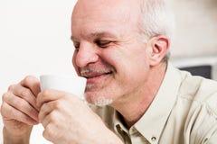 Grimacerie de l'homme sirotant de la tasse de thé Image stock