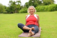 Grimacerie de la femme supérieure s'asseyant sur le tapis de yoga image libre de droits