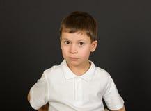 Grimacing boy portrait on black Stock Photography