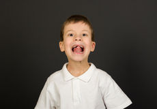 Grimacing boy portrait on black Stock Image