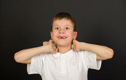 Grimacing boy portrait on black Stock Image