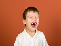 Grimacing boy portrait on brown Stock Photos