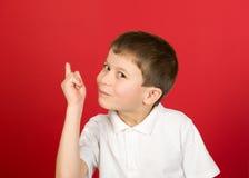 Grimacing boy portrait on red Stock Photo
