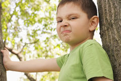 Grimacing boy between trees Stock Photo