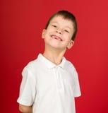 Grimacing chłopiec portret na czerwieni Fotografia Royalty Free