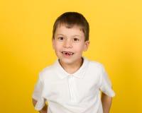 Grimacing chłopiec portret na kolorze żółtym Fotografia Stock