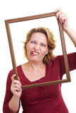 Grimacing in a frame. Happy woman holding a wooden frame in front of her face Stock Photography