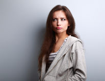 Grimacing fun young woman thinking and looking fun Stock Image