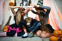 Grimacing girls scaring friend at Halloween party. Joyful artistic girls holding hands above friend while scaring boy covering under cape at hilarious Halloween Stock Images