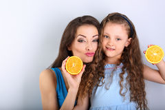 Grimacing humor young mother and cute long hair daughter holding Stock Photos