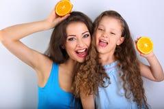Grimacing joying fun young mother and cute long hair daughter ho Stock Photography