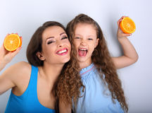 Grimacing joying fun young mother and cute long hair daughter ho. Lding slices of fresh bright oranges in hands and playing the ape. Healthy and diet lifestyle Stock Photos