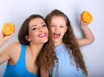 Grimacing joying fun young mother and cute long hair daughter ho Stock Photos