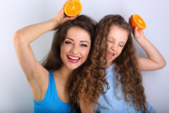 Grimacing joying humor young mother and cute long hair daughter Royalty Free Stock Images