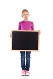 Grimacing schoolgirl standing with blackboard. Royalty Free Stock Image