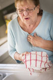 Senior Adult Woman At Sink With Chest Pains Royalty Free Stock Photography