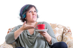 Grimacing woman gesturing to cup of coffee Stock Photo