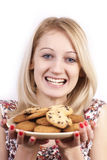Grimacing woman with plate of cookies. On white background stock photography