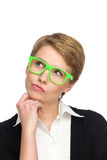 Grimacing young woman in green glasses looking up. Stock Image