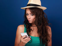 Grimacing young woman in hat looking on mobile phone with questi Royalty Free Stock Images