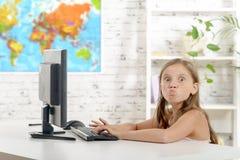 Grimaser för barnskolaflicka i klassrumet arkivbilder