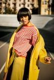 Grimassen getrokken Afrikaanse Amerikaanse dame met glad haar en omvangrijke oorringen stock foto's