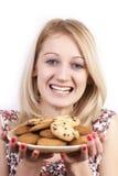 grimassen trekkende vrouw met plaat van koekjes Stock Fotografie