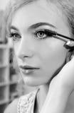 Grimeur die mascara op het oog van het model toepassen Stock Foto's