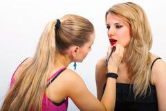 Grimeur die mascara op lippen toepassen Stock Foto
