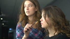 Grimeur die met borstel aan modelgezicht werken Het toepassen van toon op huid stock video