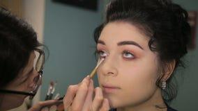 Grimeur die op make-up op de modelogen van ` zetten s stock video