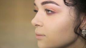 Grimeur die op make-up op de modelogen van ` zetten s stock footage