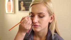 Grimeur die samenstelling doen aan jonge vrouw stock video