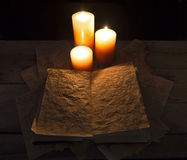 Grimoire book and candles. Halloween still life with open magic book and three candles on the table in the darkness Stock Photo
