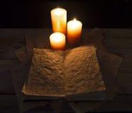 Grimoireboek en kaarsen Stock Foto