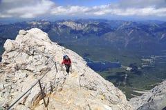 Grimpeur à la croix sur le sommet de la montagne de Zugspitze, Allemagne photos libres de droits