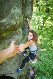 Grimpeur aidant le grimpeur féminin à atteindre une crête de montagne Image libre de droits