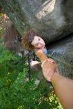 Grimpeur aidant le grimpeur féminin à atteindre une crête de montagne Photographie stock libre de droits
