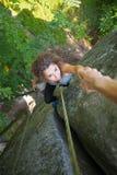 Grimpeur aidant le grimpeur féminin à atteindre une crête de montagne Images libres de droits