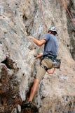 Grimpeur d'homme s'accrochant à une falaise Images libres de droits