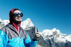 Grimpeur de montagne heureux ayant le rafraîchissement de la tasse thermo photo libre de droits