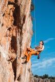Grimpeur de roche accrochant sur la corde de prise au-dessus des montagnes Photo stock