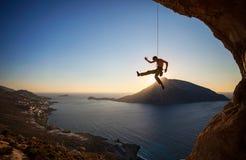 Grimpeur de roche accrochant sur la corde tandis que menez s'élever photographie stock